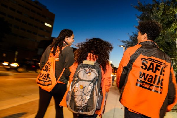 Two SAFEwalk staff (in bright orange) walk with a student as the night begins.