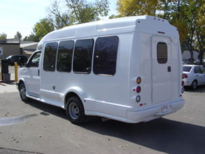 Image of the left side of the white bus, shot from the rear. UW decals are visible.