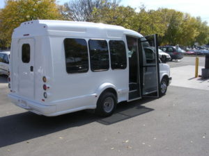Image of the left side of the white bus, shot from the back. Loading door is open and UW decals are visible.