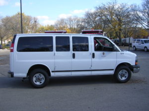 Image of a white 8 passenger van with UW decals.