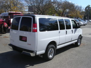 Image of the white fleet passenger van's right side, shot from behind.