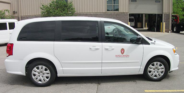 Side shot of a white minivan with UW decals.