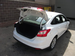 Outside shot of the small fleet car with its trunk open.