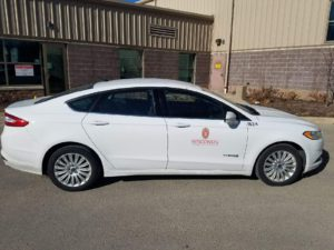 White Ford Fusion hybrid electric sedan with UW decals.